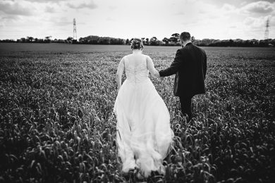 the bride and groom in the corn field at shustoke farm barns in warwickshire