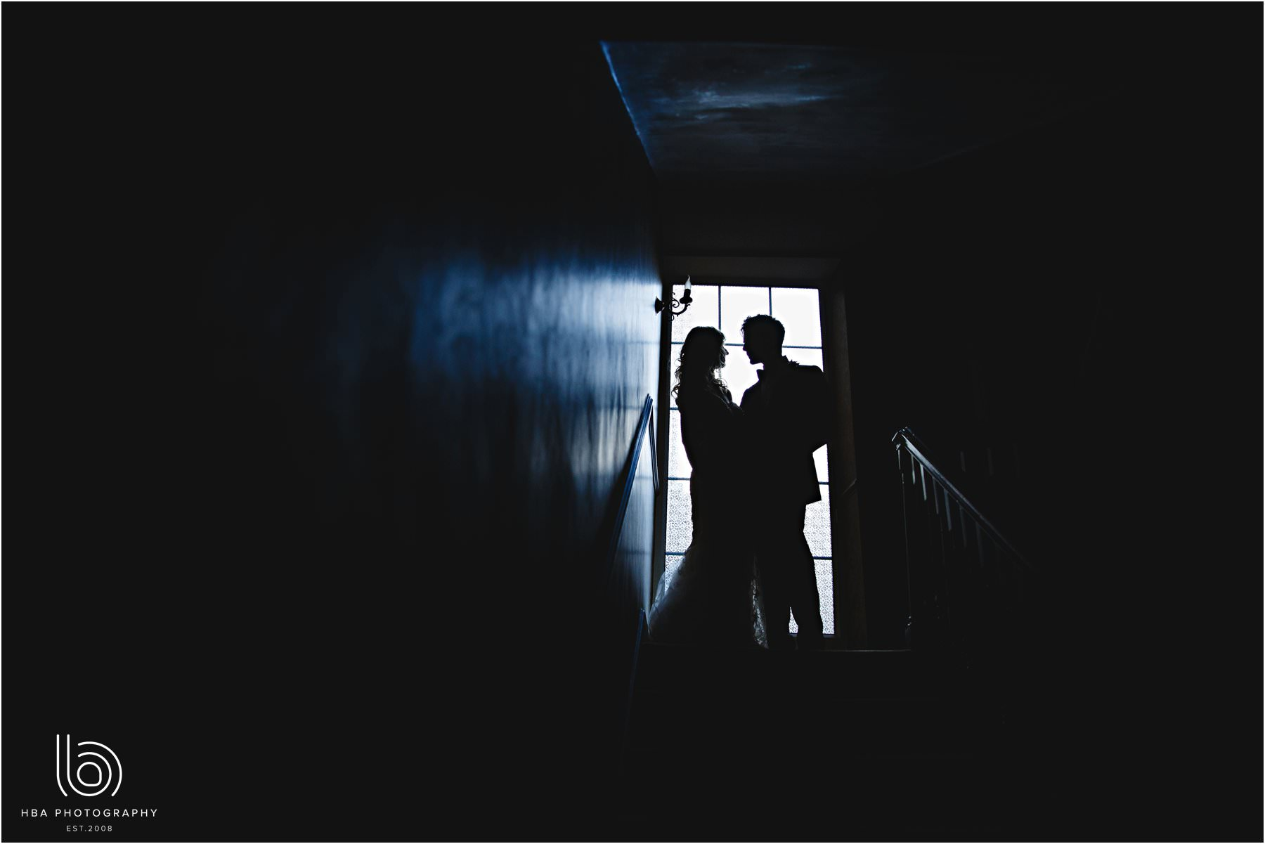 the bride & groom in silhouette in the hallway