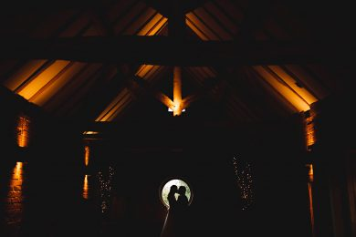 the bride and groom stood in darkness at Shustoke Farm Barn on their wedding day on