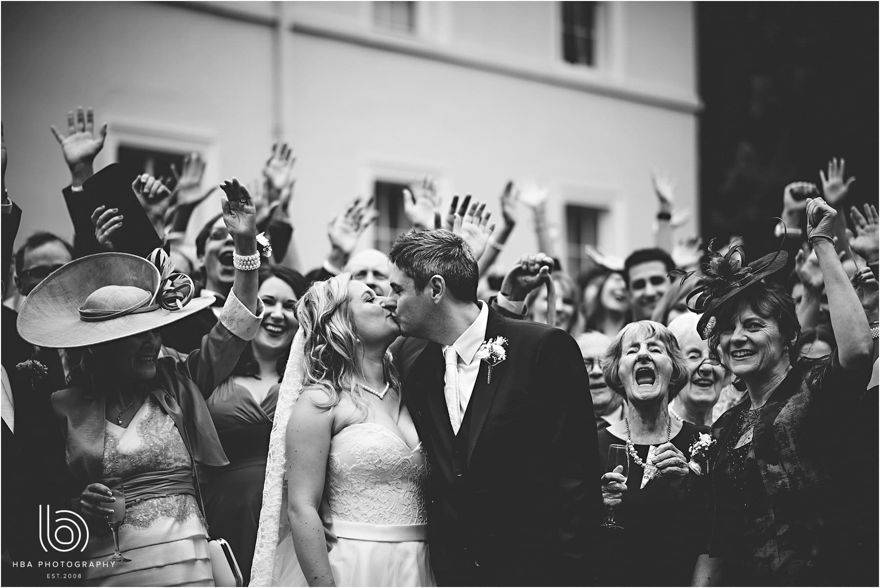 guests cheering as the bride and groom kiss for the first time