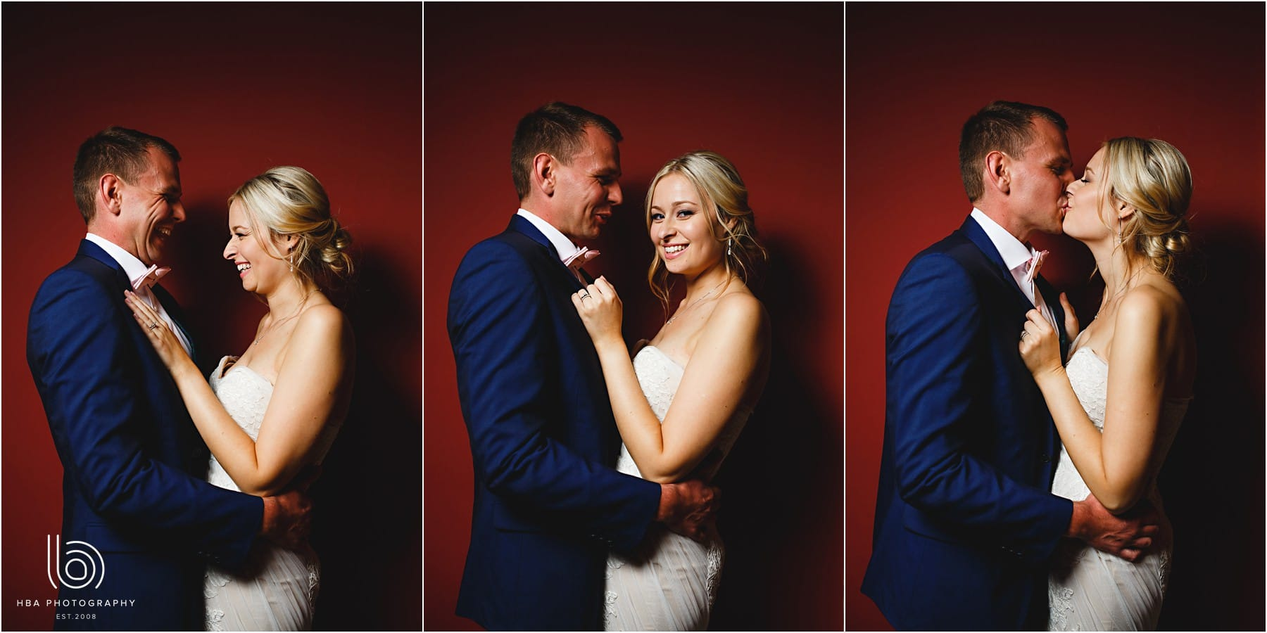 the bride & groom by a red wall