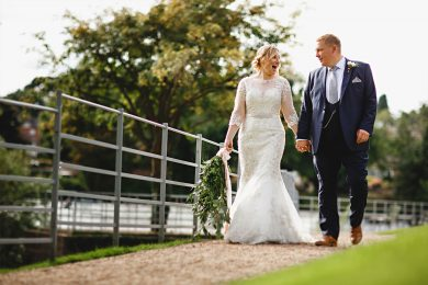 the bride and groom walking by the river at The West Mill