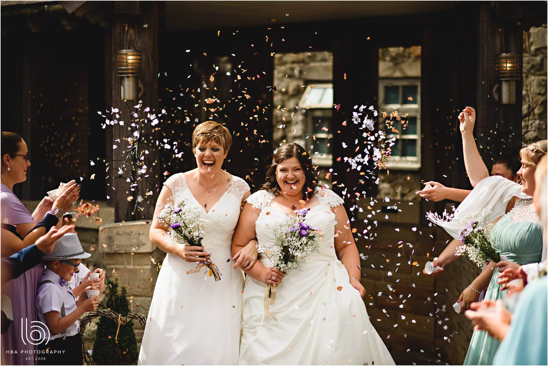 the two brides getting covered in confetti
