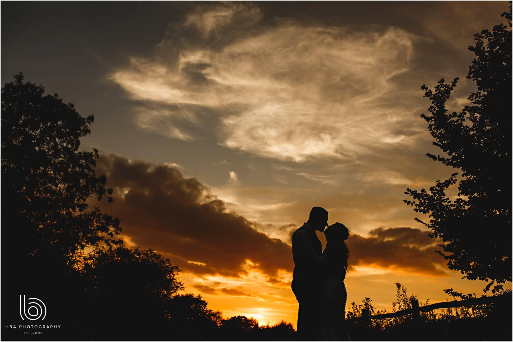 the bride and groom in silhouette at sunset