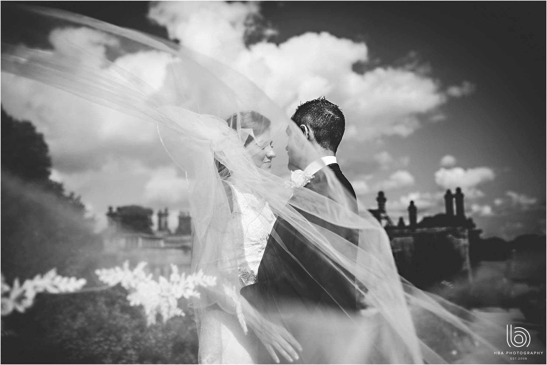 the bride & groom with the veil blowing in the wind