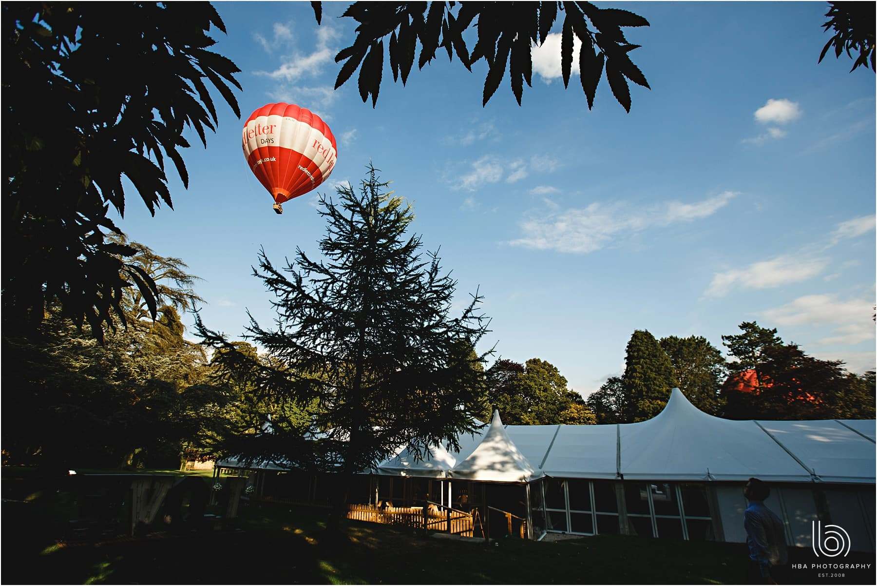 the marquee at Tissington Hall with a hot air balloon in the background