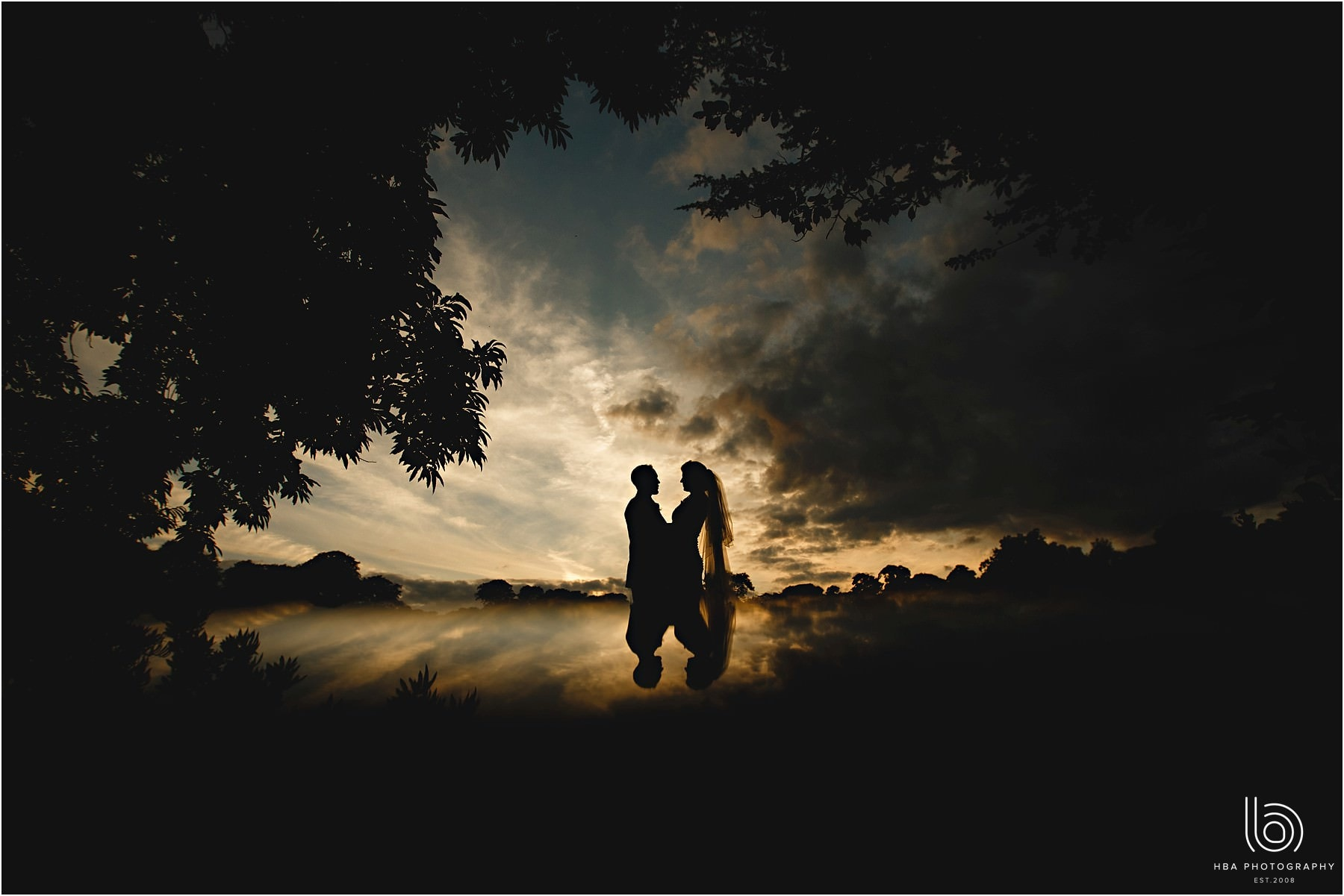 the bride & groom in silhouette in the sunset