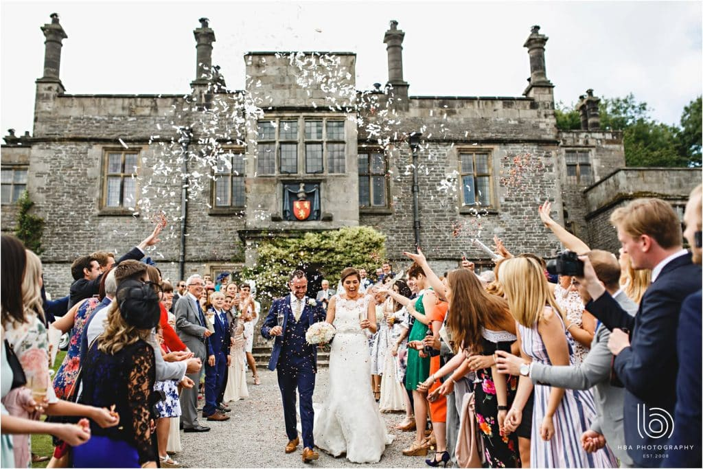 the bride & groom getting covered in confetti outside Tissington Hall