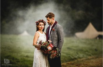 Bride and groom stood together in a misty field