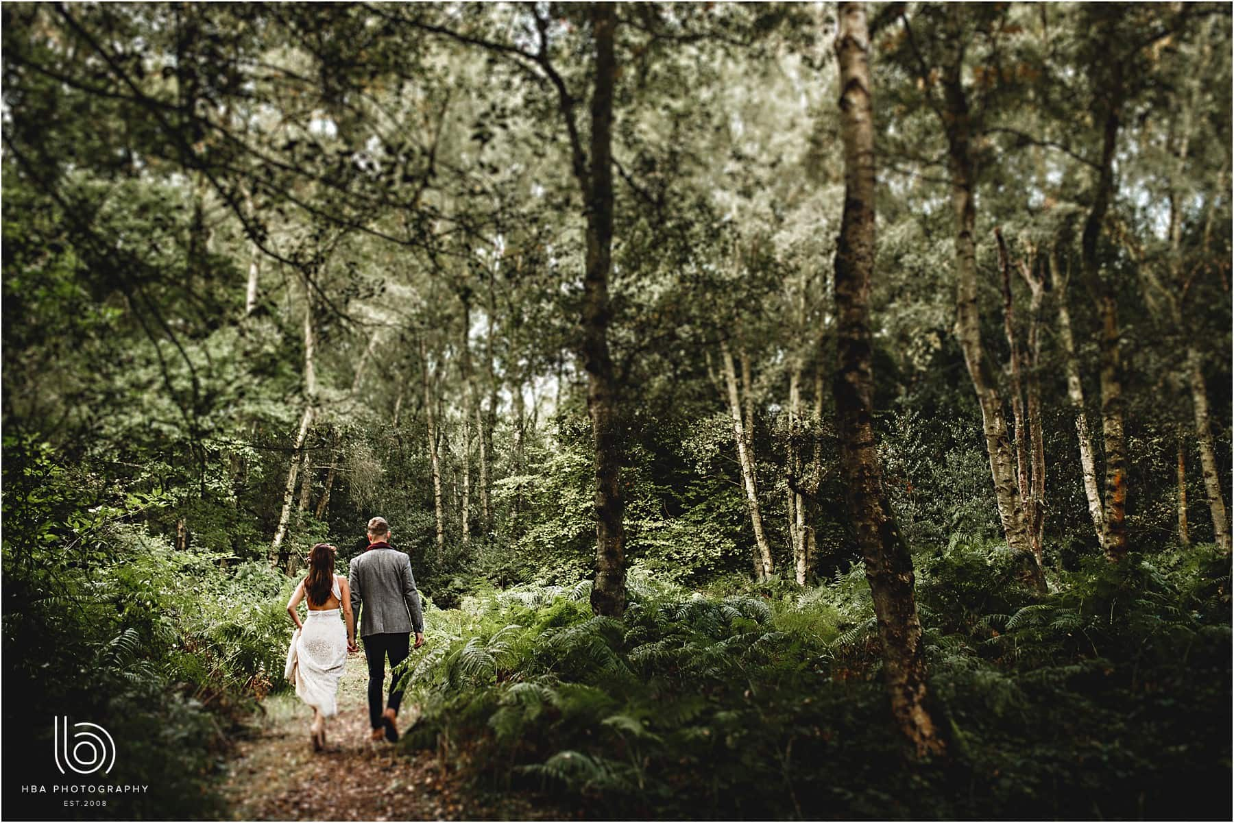 Bride and groom walking through the woodland