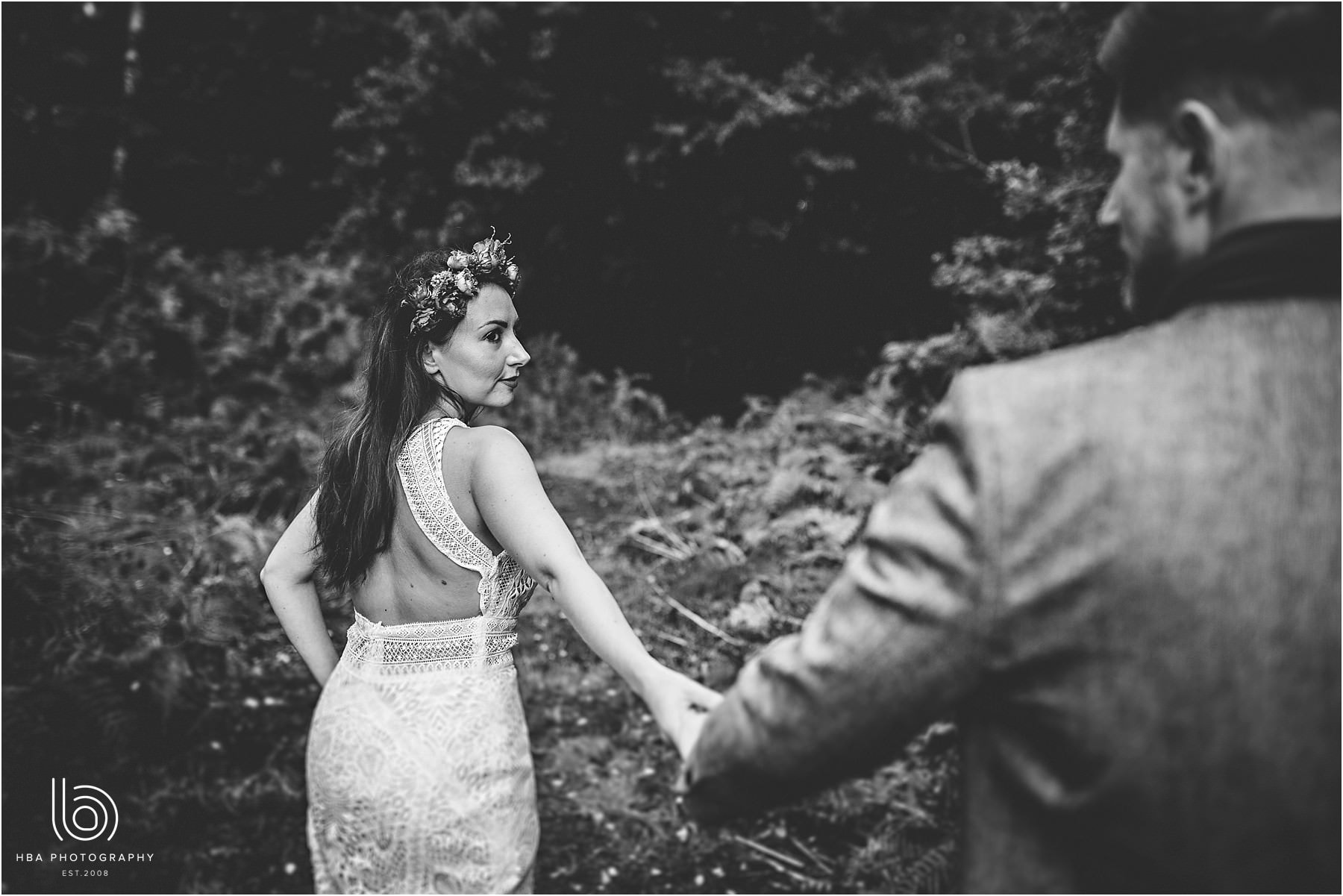 The bride and groom walking into the woods on their wedding day