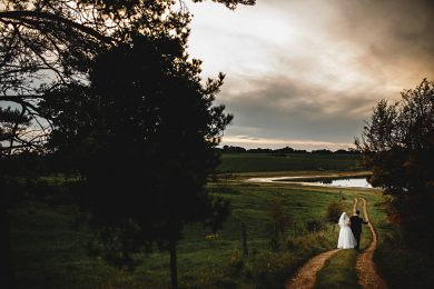 the bride and groom wlaking down the lane and Blithfield Barns