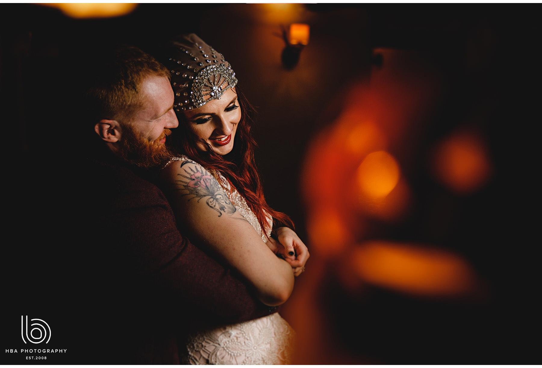 the bride & groom cudding in the orange light
