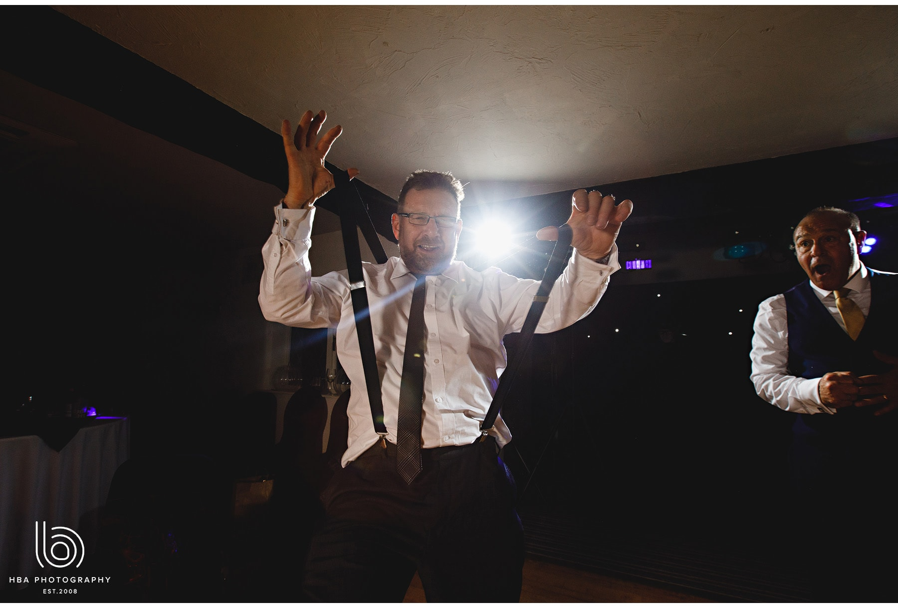 wedding guest pulling his braces as he dances.