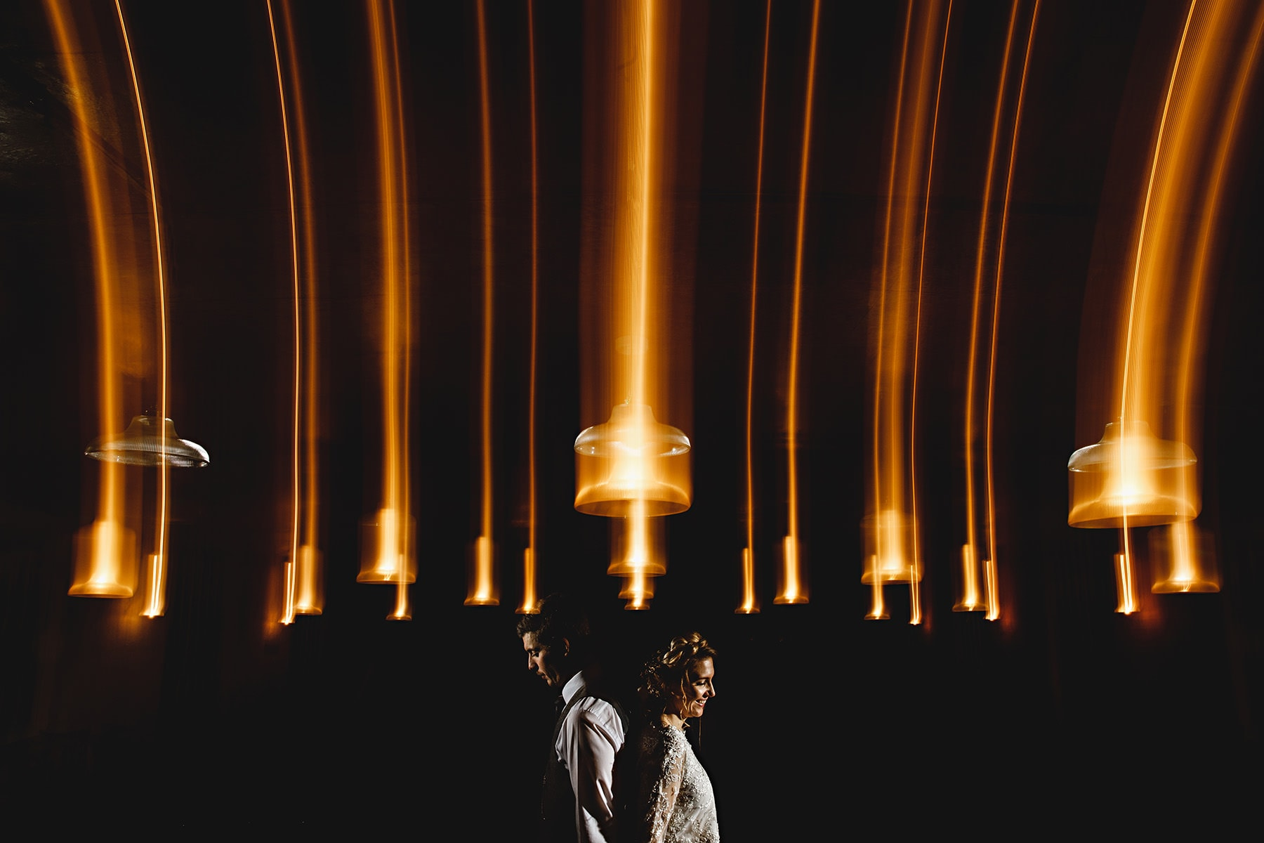the bride and groom stood together in dark orange lights at The West Mill on their wedding day in Derbyshire