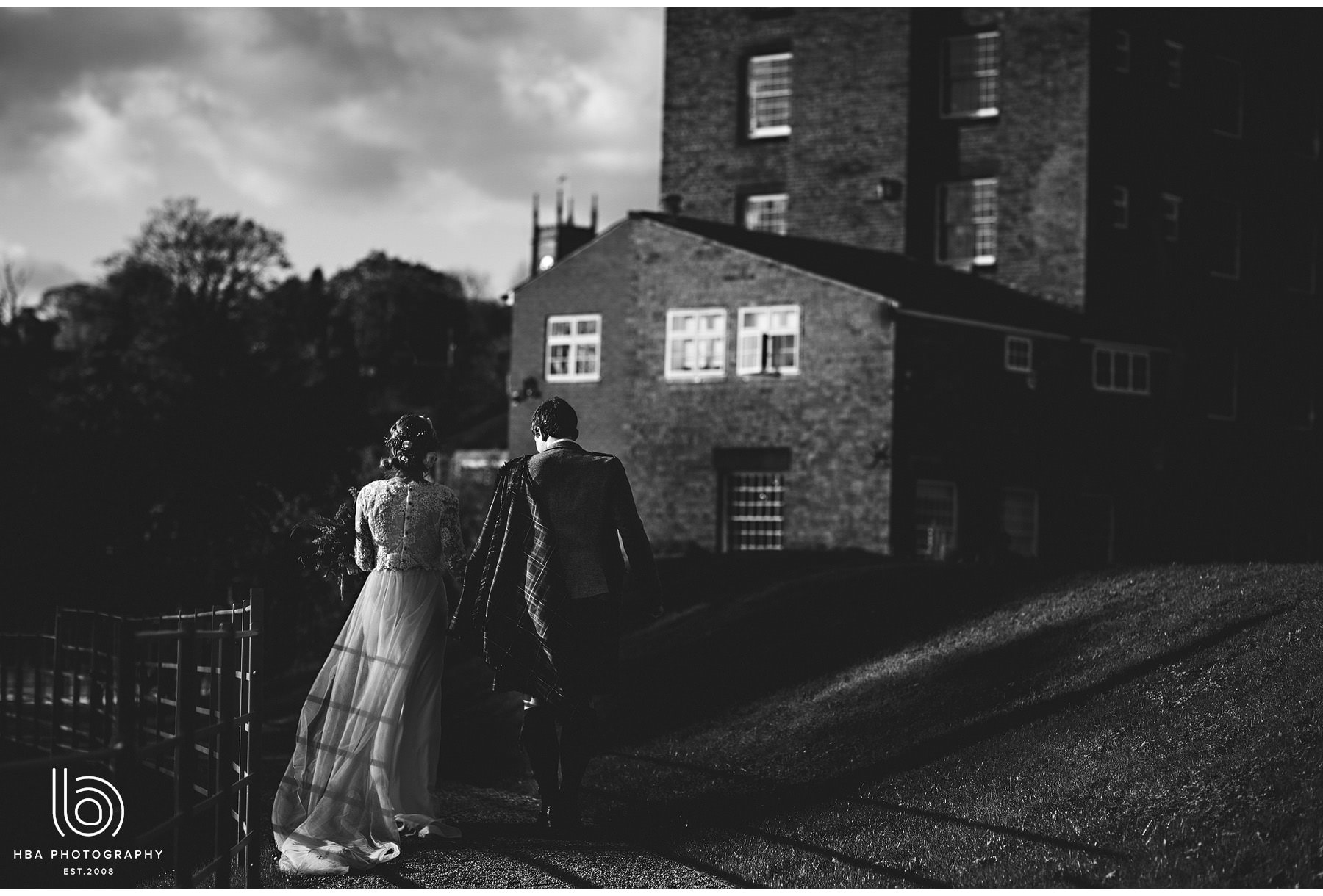 the bride & groom walking by the West Mill