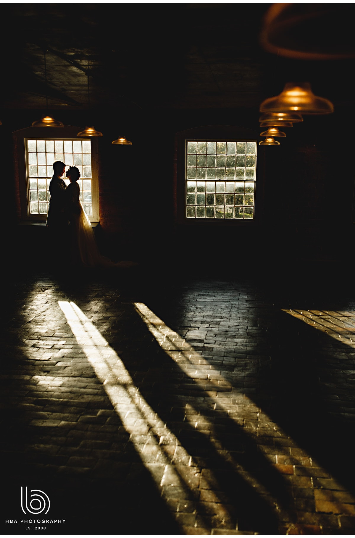 the bride & groom with the sun shing through the window