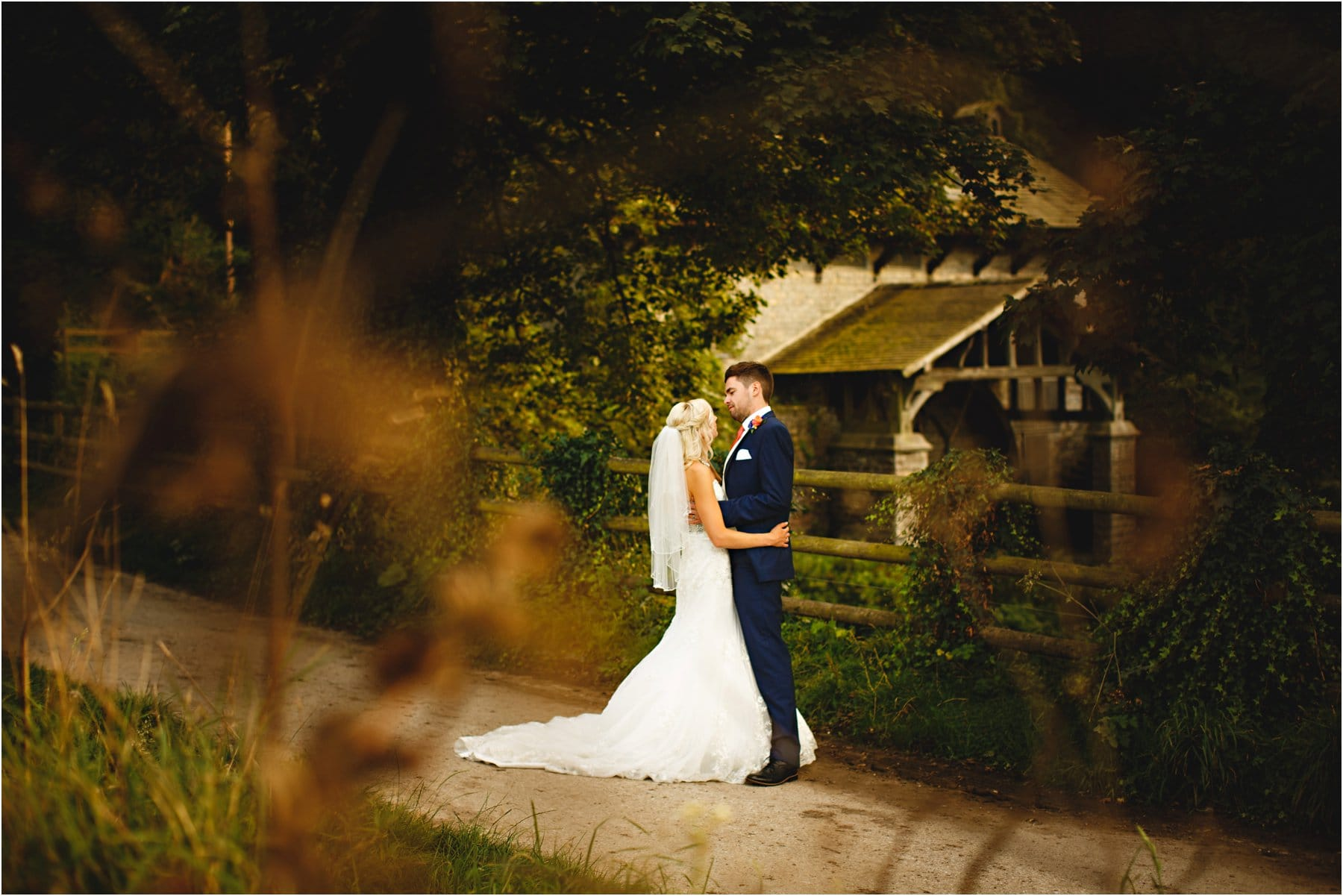 the bride & groom by the water mill