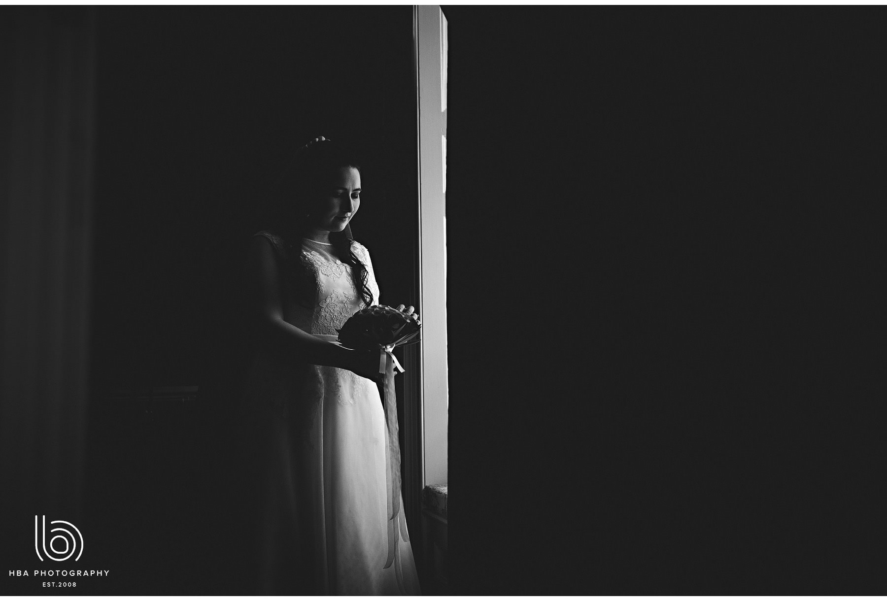 the bride in the window looking at her flowers