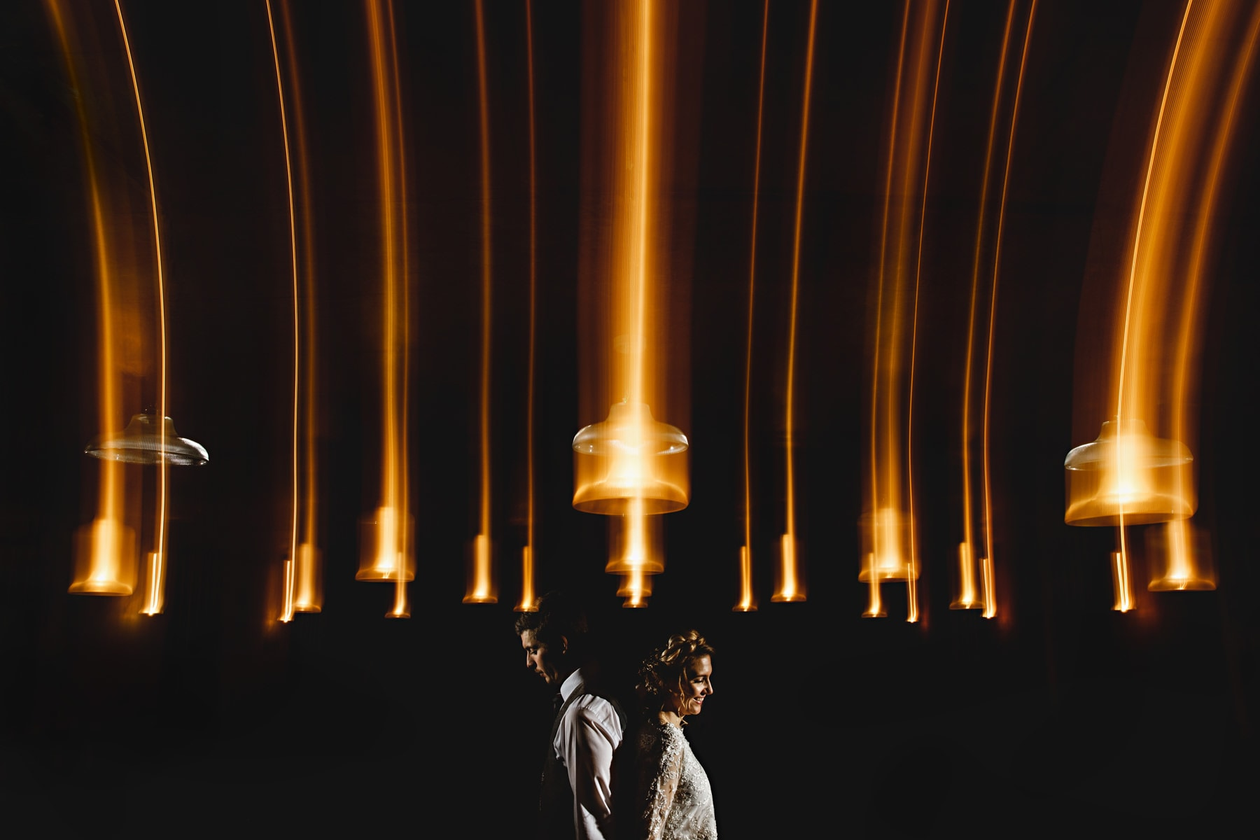 bride and groom under orange lights