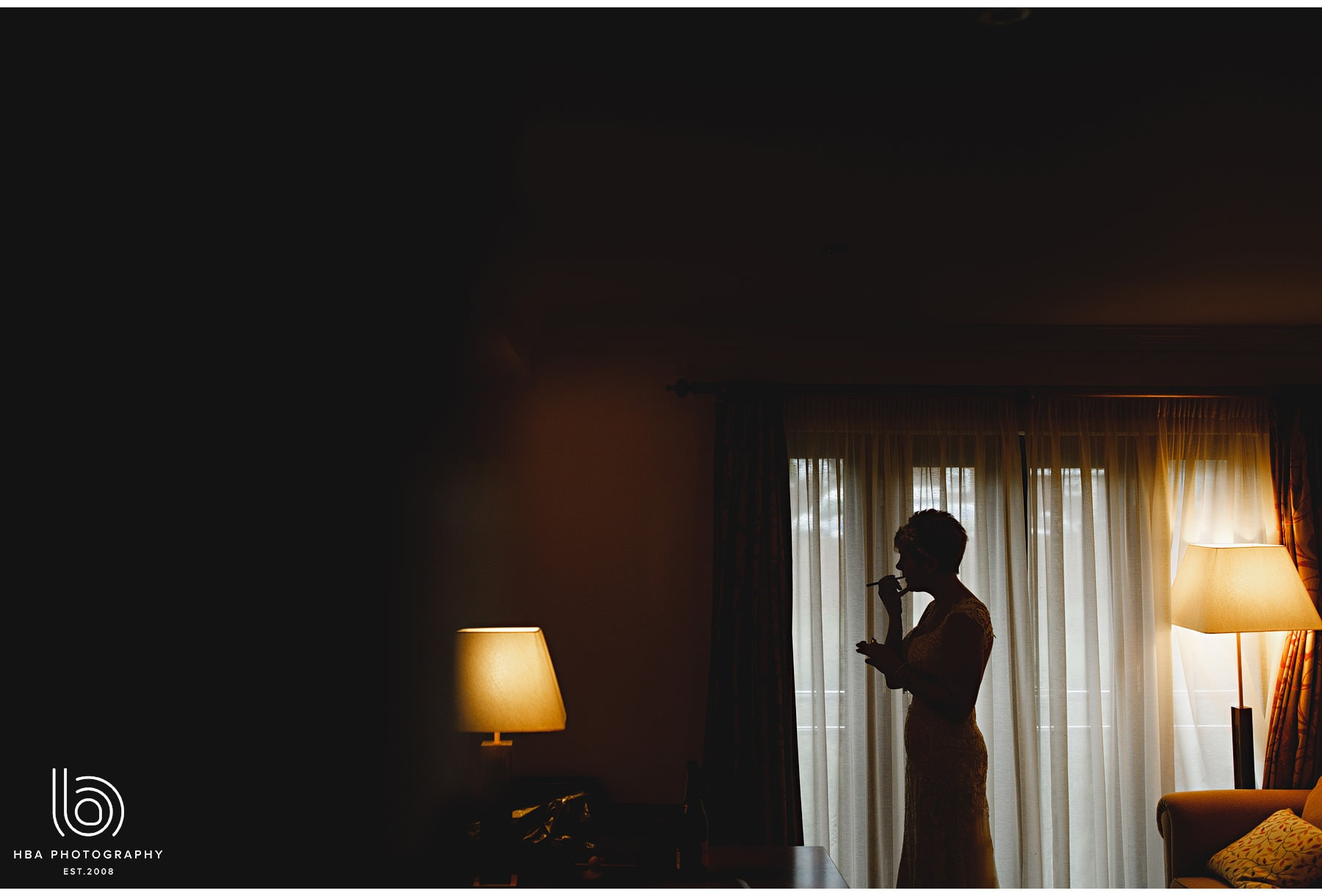 the bride in silhouette doing her lipstick