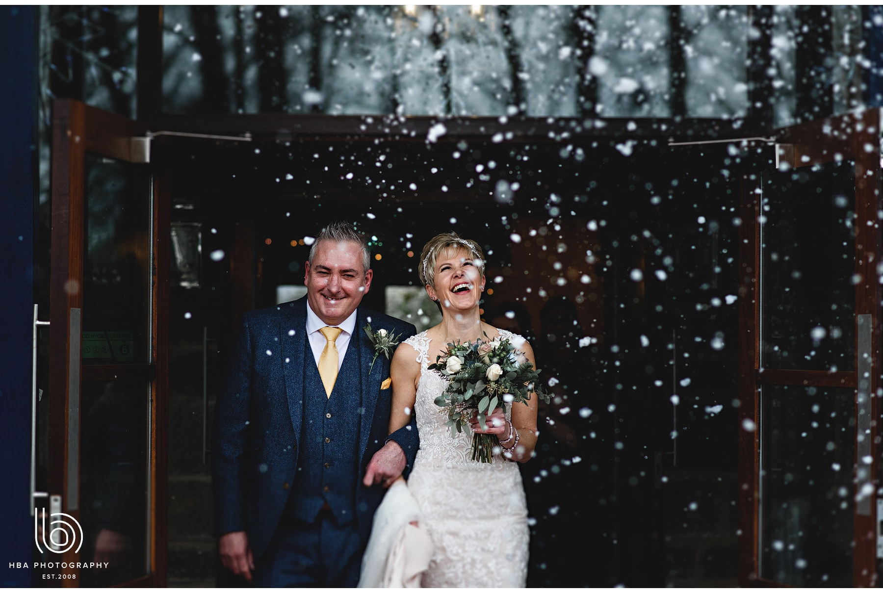 the bride & groom getting covered in snow