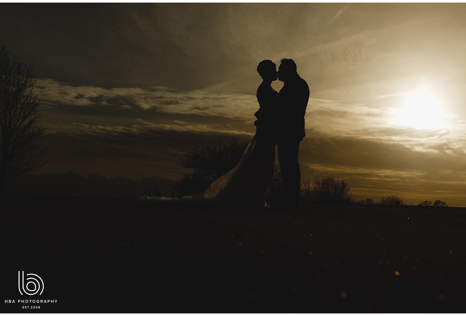 the bride & groom in silhouette against the sunset