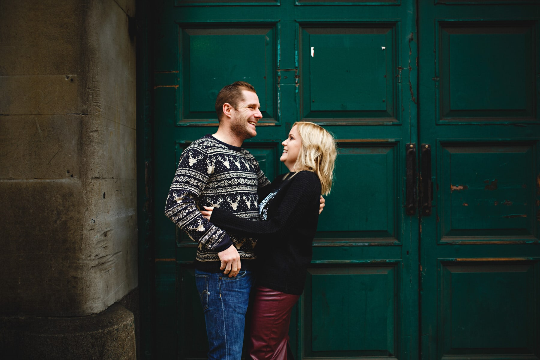 couple stood together in front of a green door in the city