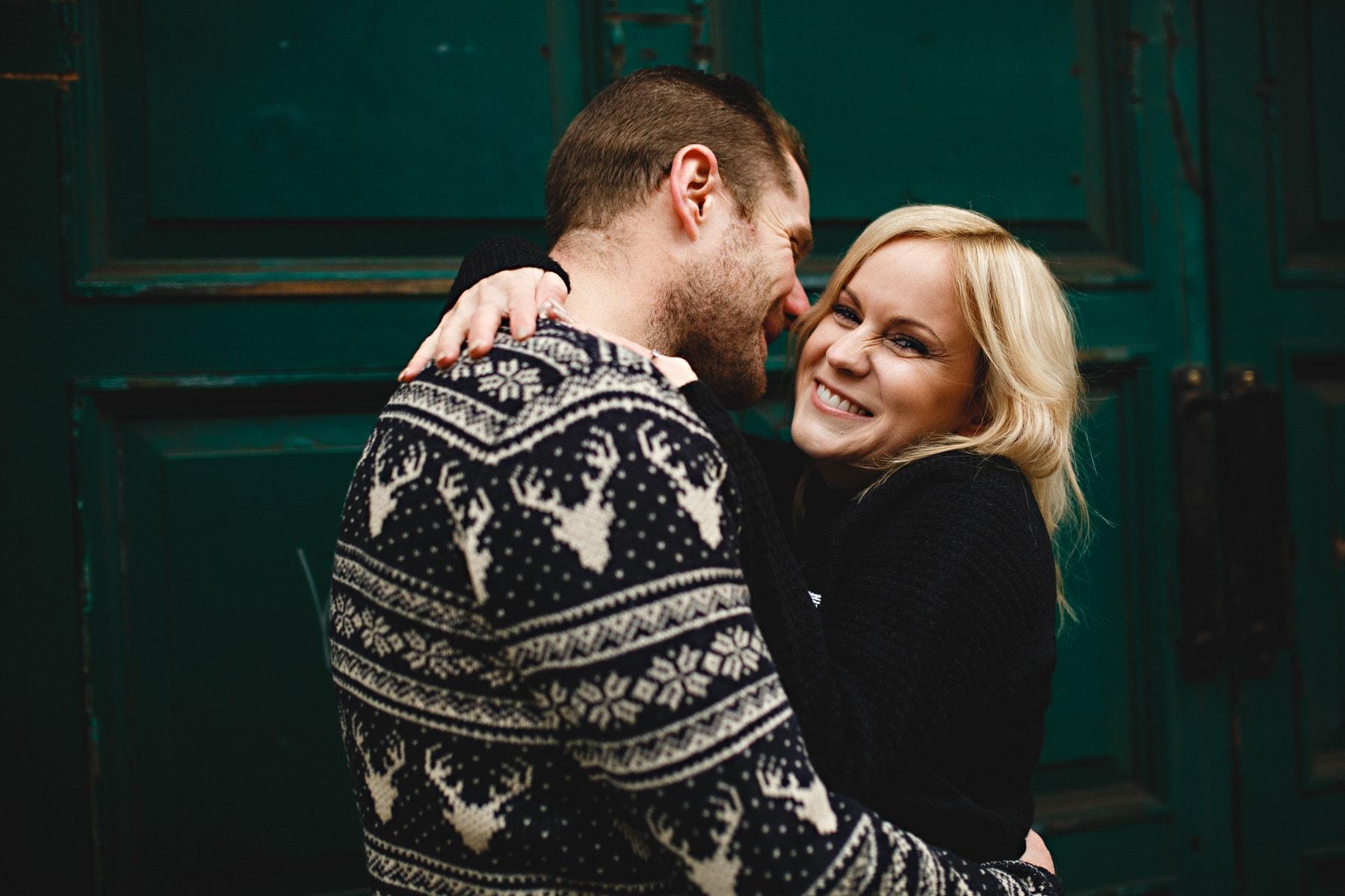 hugging together against a green door