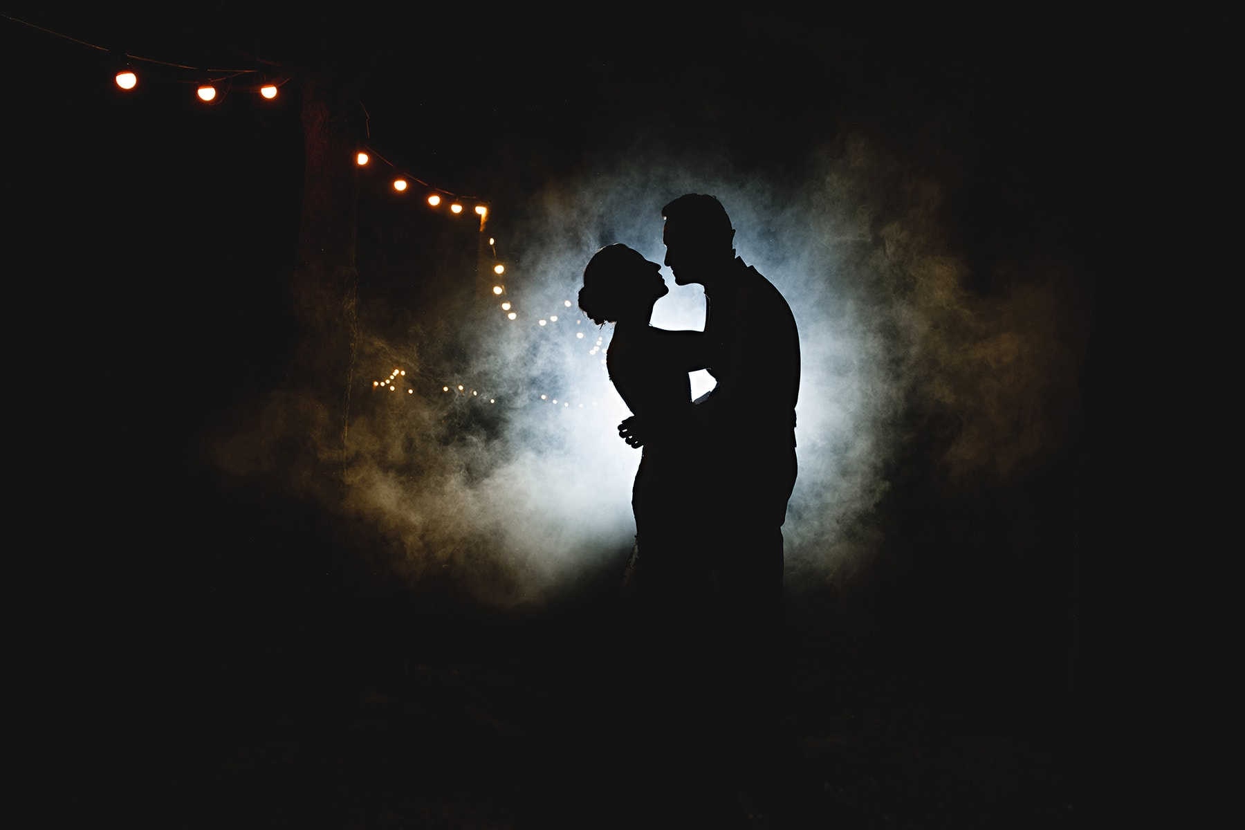 The bride and groom in smoke at Shustoke Barns in Warwickshire
