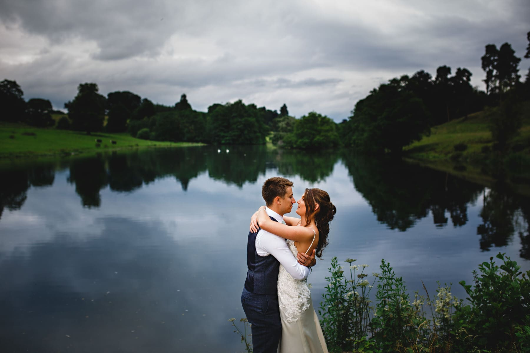 bride and groom against the lake at osmaston