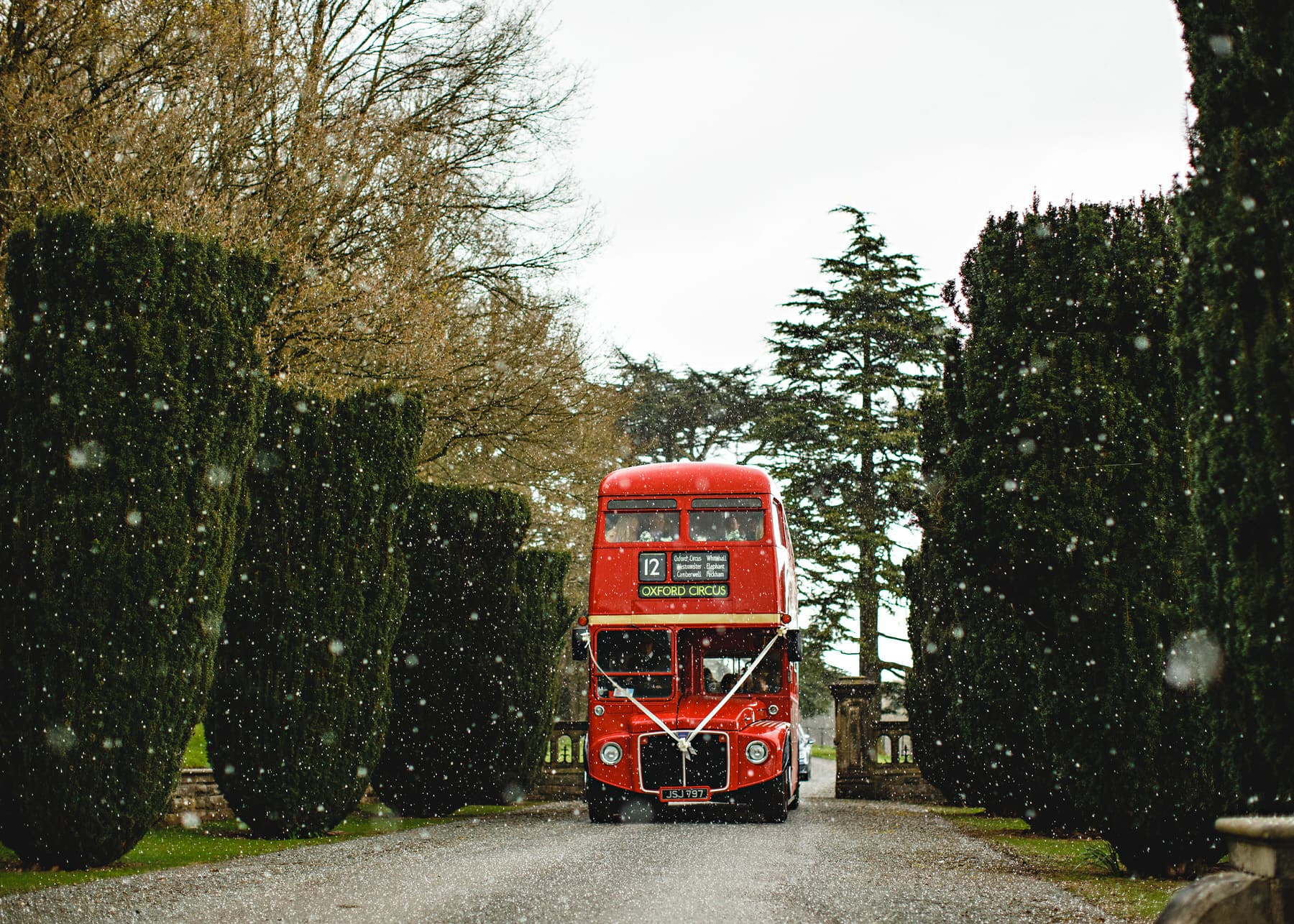 red bus arriving in the snow at Osmaston Park in Derbyshire