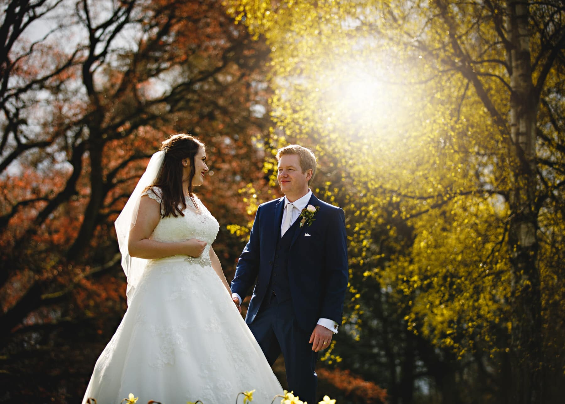 bride and groom in the autumn sun Osmaston Park in Derbyshire