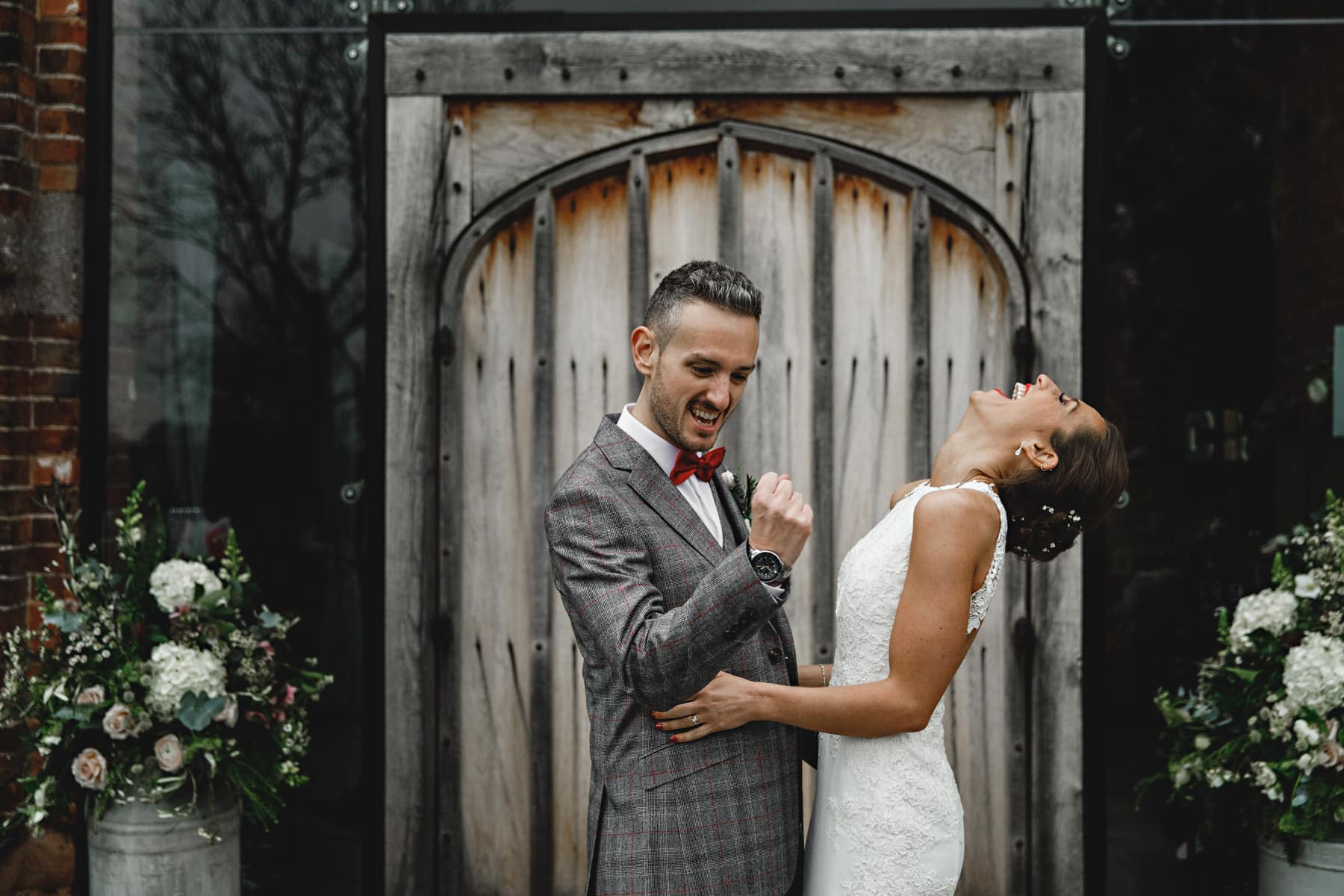 the bride and groom laughing outside the wooden doors at Shustoke Barns in Warwickshire
