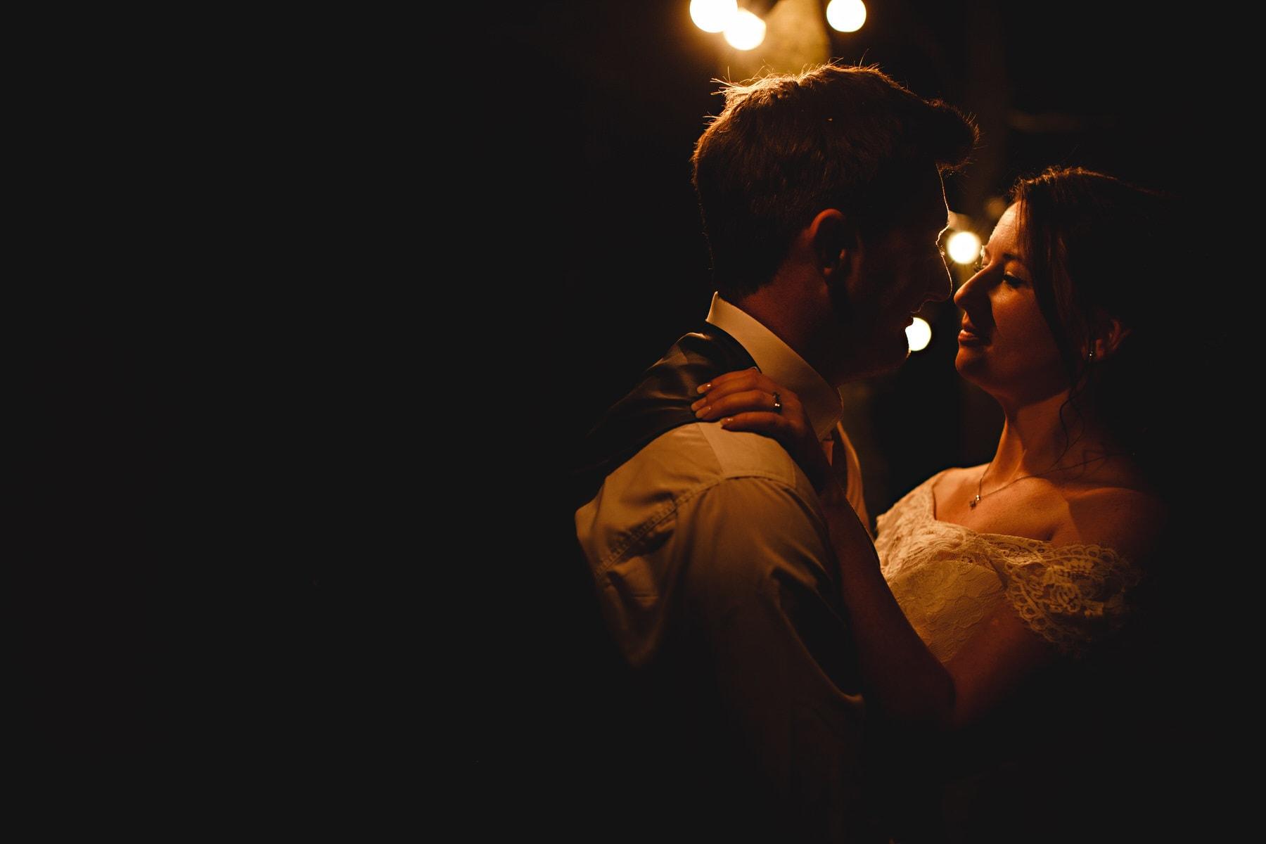 the bride and groom in orange festoon lights at Shustoke Barns in Warwickshire