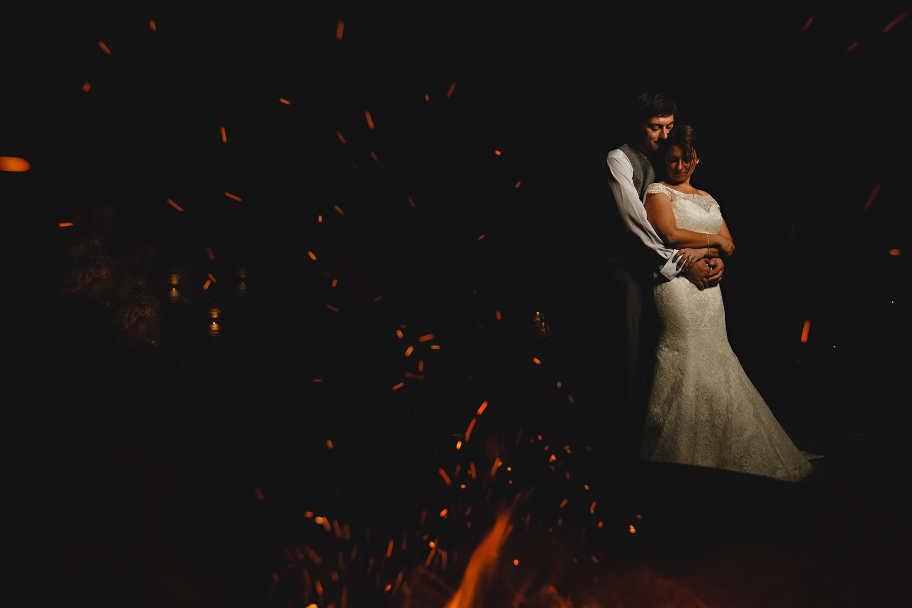 the bride and groom hugging by the fire pits at Shustoke Barns in Warwickshire