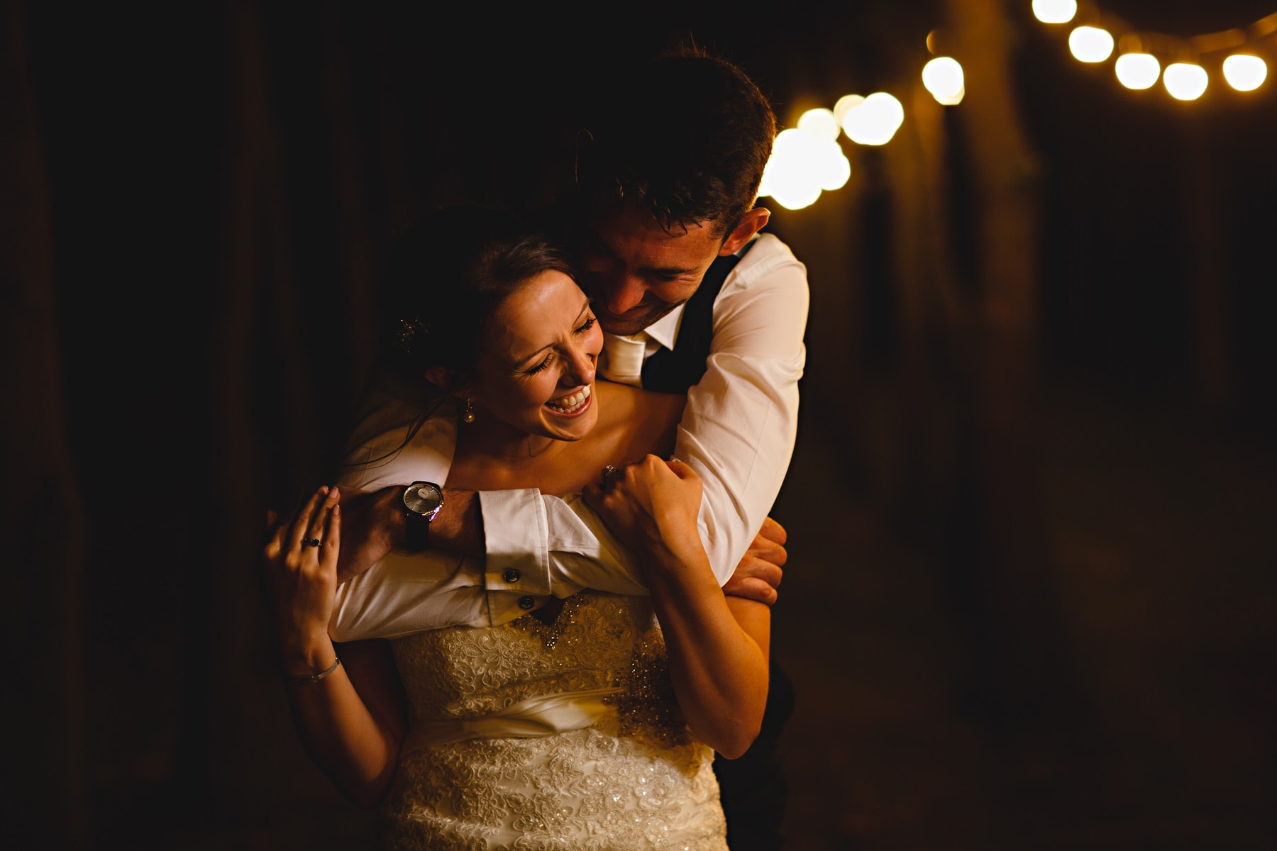 bride and groom huggin in the dark orange festoon lights at Shustoke Barns in Warwickshire