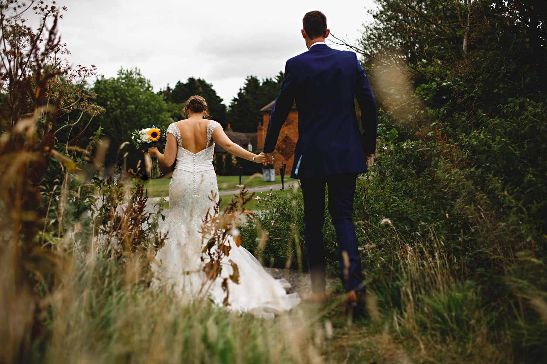 bride and groom walking out of the field at Shustoke Barns in Warwickshire