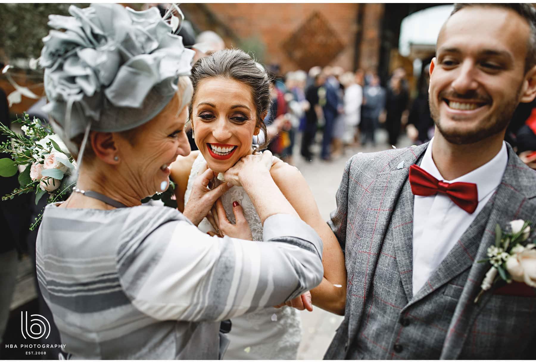 the bride's mum putting confetti down the bride's dress