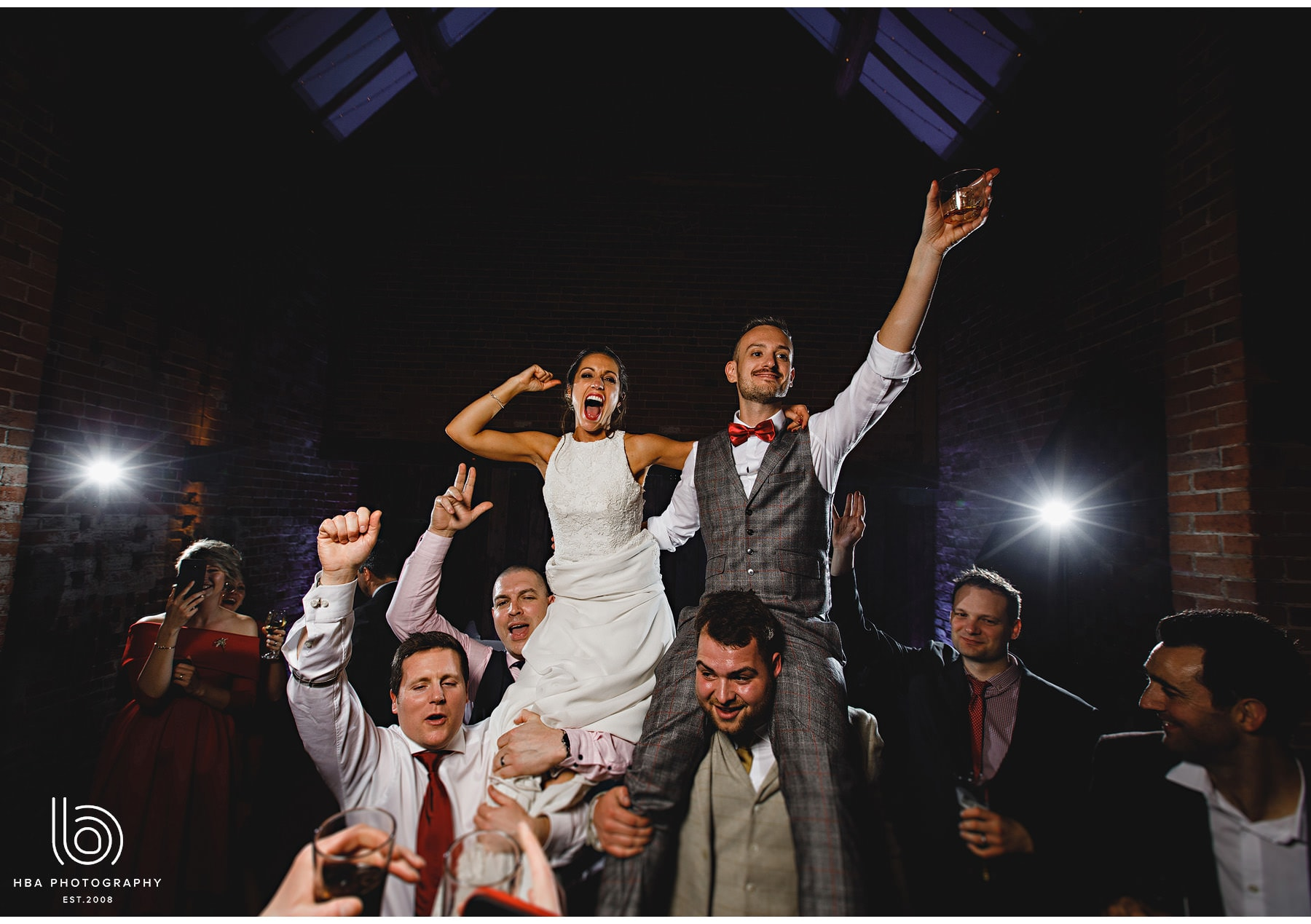 the bride and groom lifted onto friends shoulders!