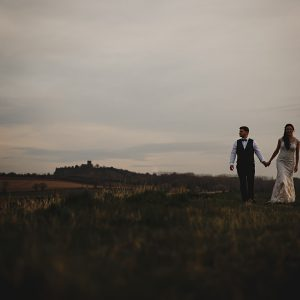 The bride and groom walking in the golden hour sunlight