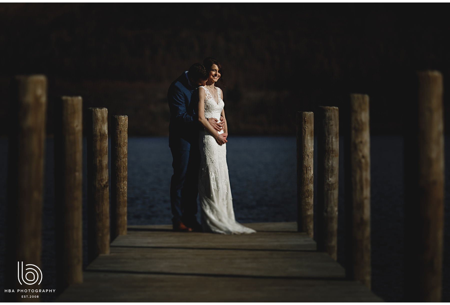 the bride & groom at the end of the pier at Derwent Water