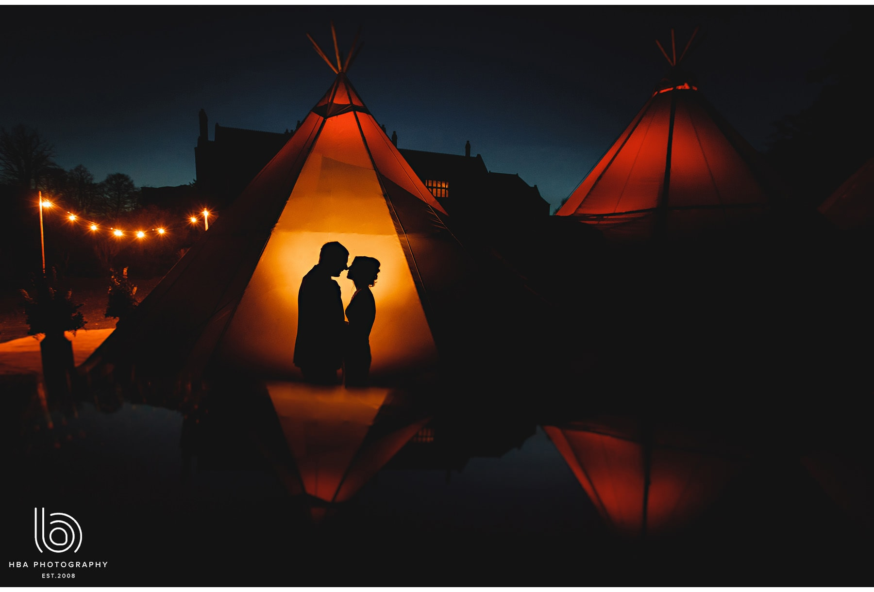 The bride & groom in silhouette against the tipi
