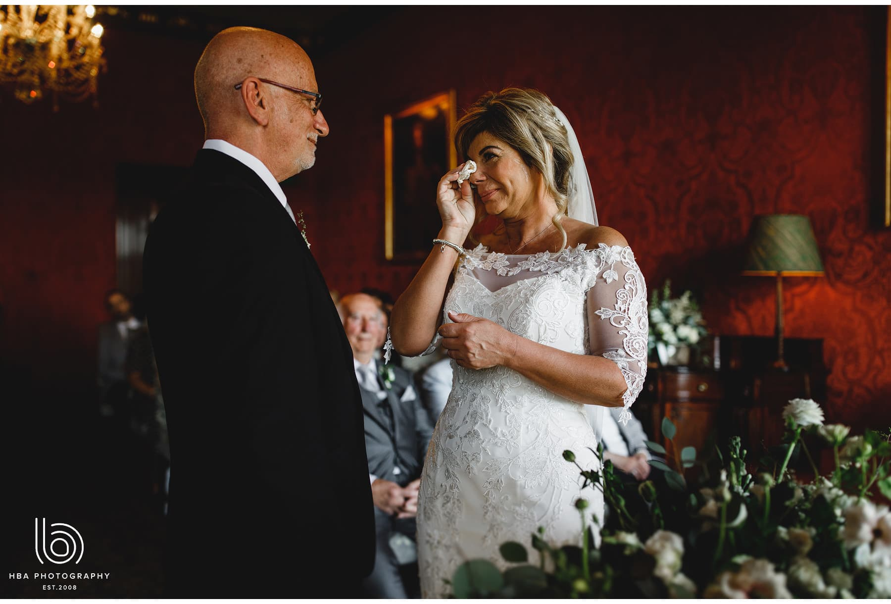 the bride wiping away tears during the ceremony