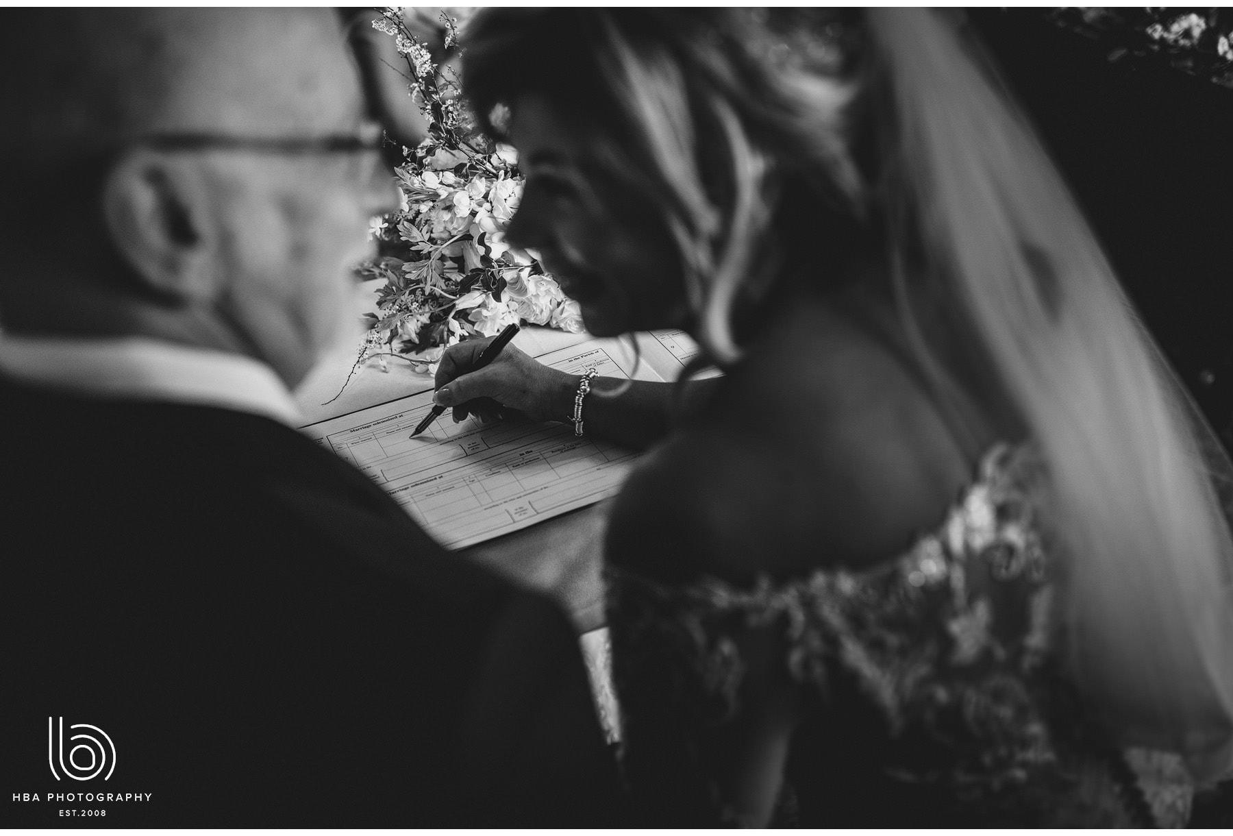 the bride & groom signing register