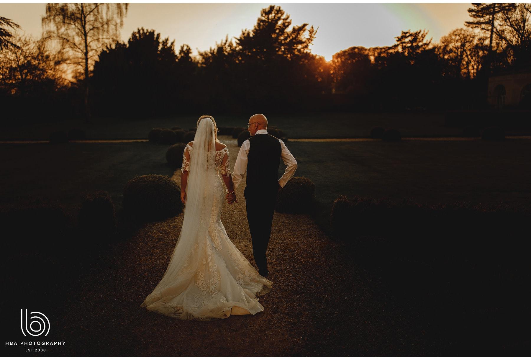 the bride & groom walking in the dusk