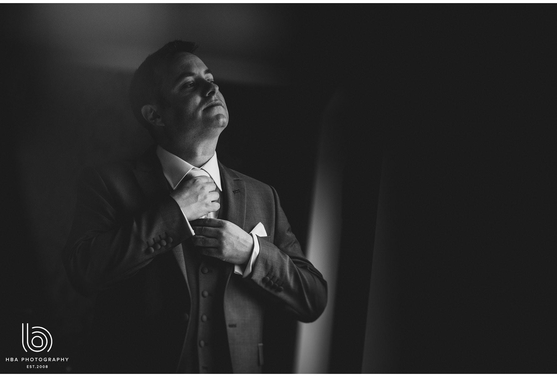 the groom doing his tie