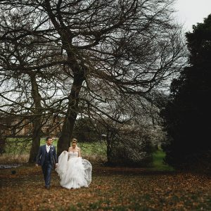 the bride and groom walking in the spring gardens at Cranage Hall in Cheshire