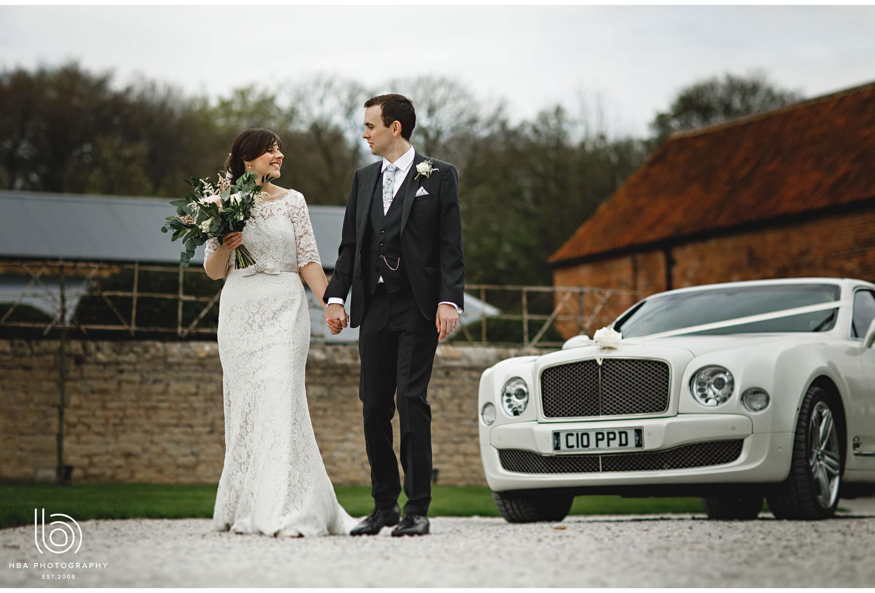 the bride & groom with the car