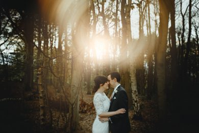 bride and groom stood in the bluebell woods at Hazel Gap on their spring wedding in golden sunlight
